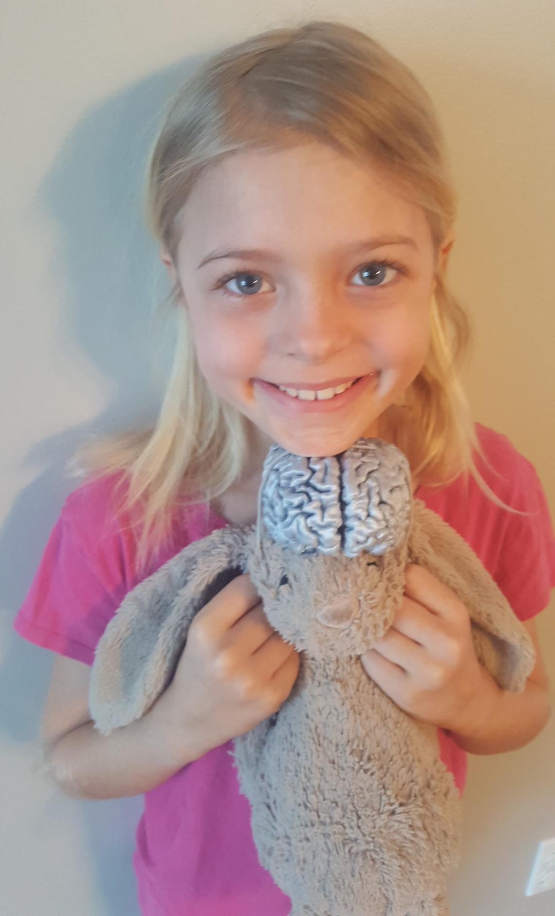 Olivia Mueller, age seven, loves to play with her favourite toy — a plastic model of her own brain that she attaches to her toy bunny.