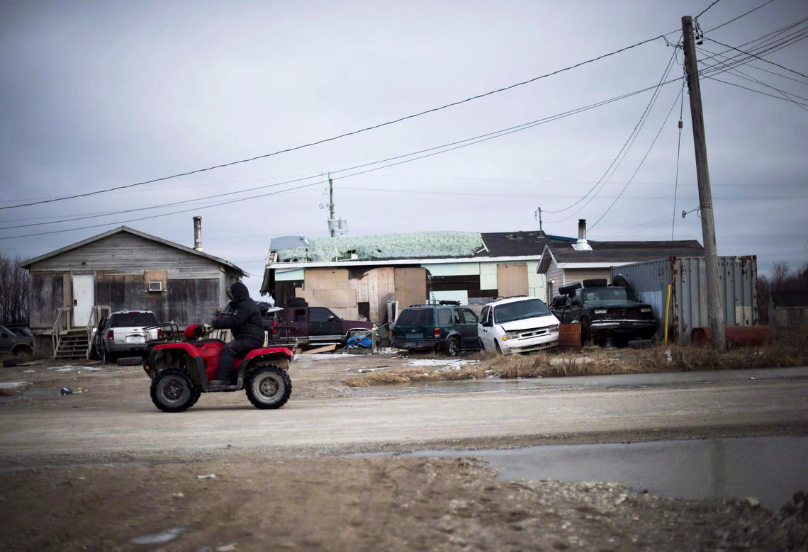 A man rides his ATV in the northern Ontario First Nations community of Attawapiskat, in April, 2016.