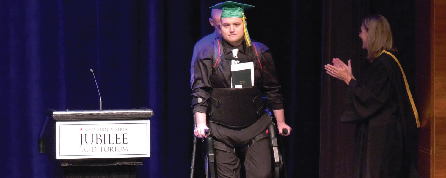 Alex McEwan, who suffered a spinal cord injury in high school, gets a standing ovation from his teachers and peers as he walks across the stage with the exoskeleton at the Jubilee Auditorium to receive his diploma in June 2018.