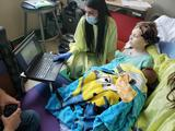A boy in the ICU using BCI, with a researcher helping