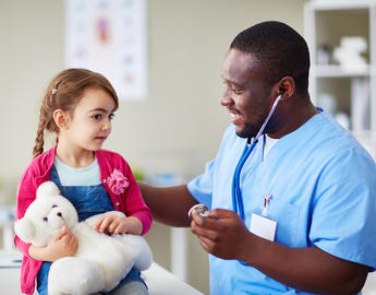 A smiling clinician works with their patient.