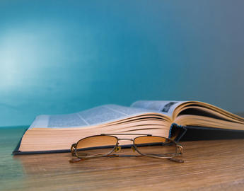 An open book sits on a wooden table next to a pair of reading glasses.